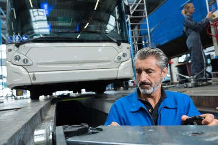 man working in bus garage