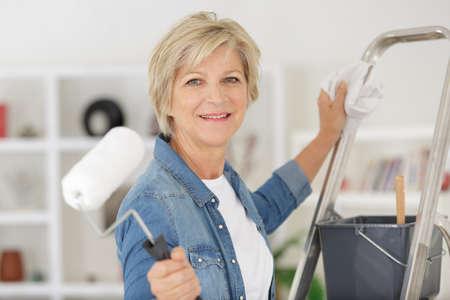 repair home elderly woman holding paint roller for wallpaper
