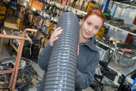 female maintenance worker carrying flexible tube Foto de archivo
