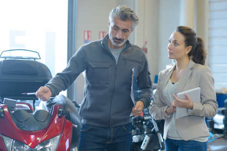 woman motrbike store seller discussing with male customer
