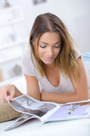 happy woman reading a magazine in the bed