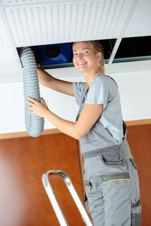 woman fitting ventilation hose into roof space Standard-Bild