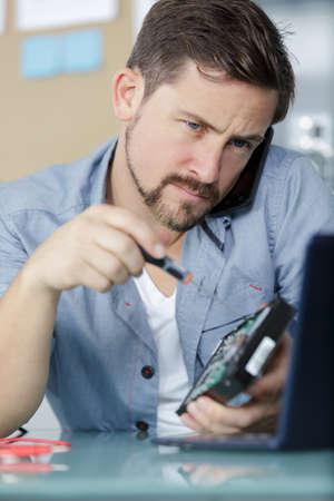 junger Techniker, der an defektem Computer arbeitet