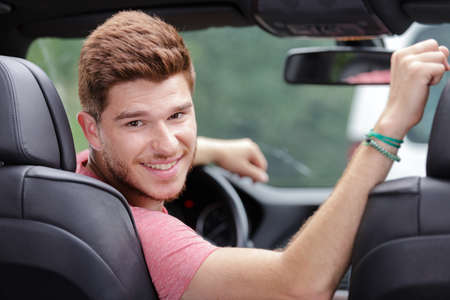 man driving car looking to back seats