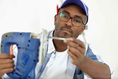 man installing new jigsaw blade