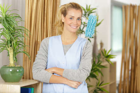 happy cleaner girl with chestnut hair working Banco de Imagens