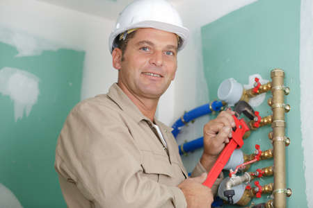 working plumber installs taps on the water heater