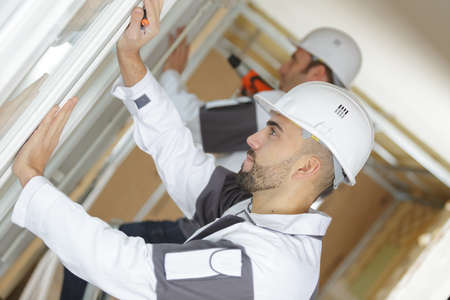 two men installing window mount at construction site
