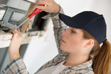 young woman working on window seal