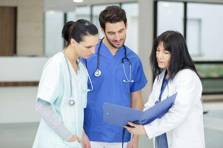 three medics looking at file and conferring