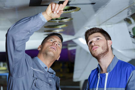 mechanics inspecting the undercarriage of an aircraft