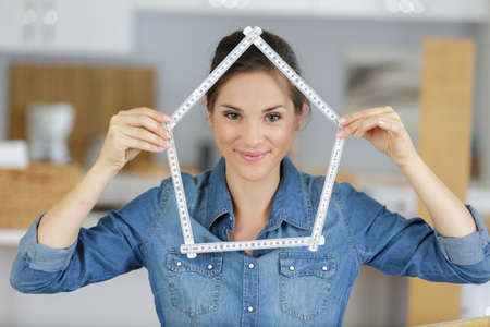 casual lady making house shape from a measuring ruler