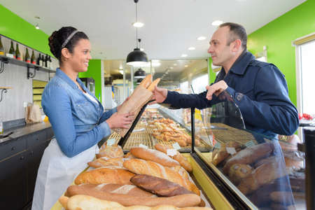 woman serving bread to male customer in bakery Imagens