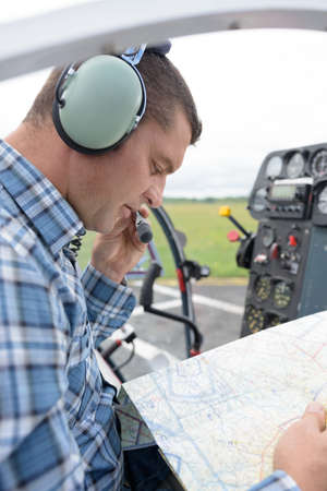 male pilot looking at map and talking into headset microphone