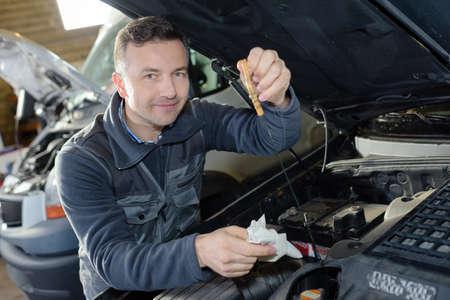 mécanicien automobile remplaçant l'huile sur le moteur dans le garage
