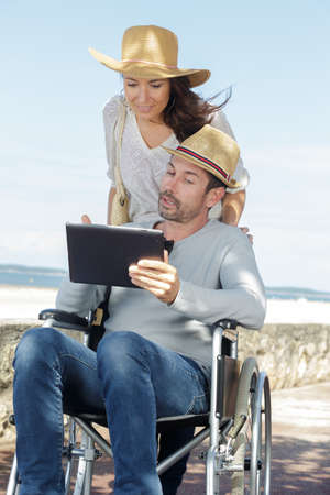 man in a wheelchair and woman are walking outdoors Zdjęcie Seryjne