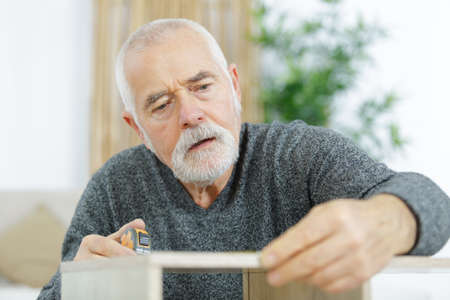 mature man assembling bed in new home Stockfoto