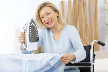 mature happy woman irons clothes Zdjęcie Seryjne