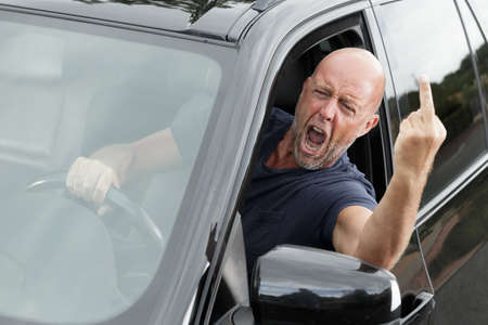 impudent man at the wheel shows an indecent gesture