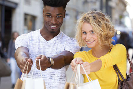 happy couple showing shopping bags