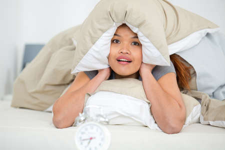 woman covering ears with pillow from alarm