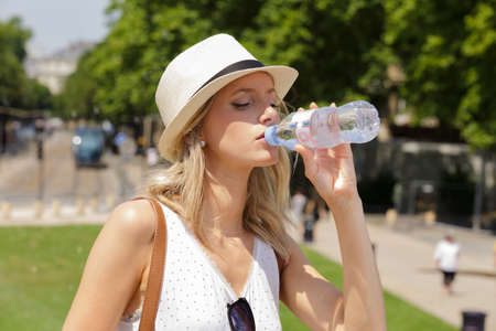 woman drinking water from plastic bottle on sunny day
