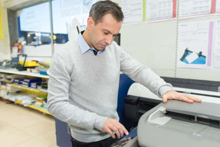 man copying paper from photocopier sunlight from window