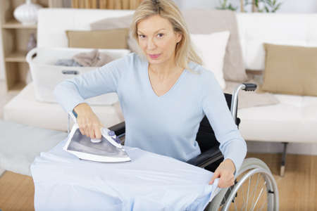smiling woman in wheelchair ironing clothes Zdjęcie Seryjne - 138521512