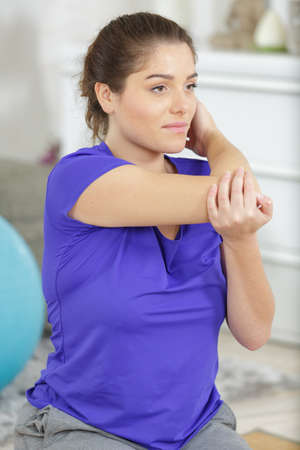 a woman stretching arms indoors