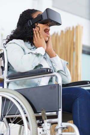 happy woman in wheelchair doing a virtual reality experience