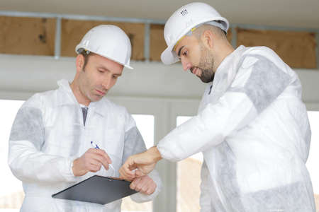 Contractors filling out paperwork on clipboard