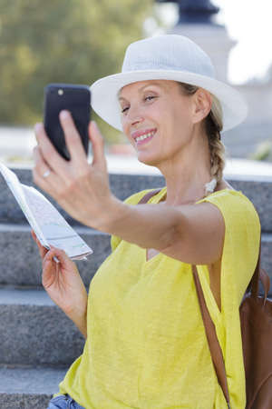 beautiful mature woman smiling happily while taking a selfie 写真素材
