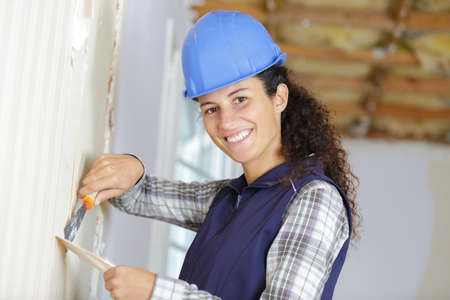 a woman removing wall paper