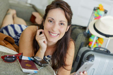 woman on sofa surrounded by travel accessories 写真素材