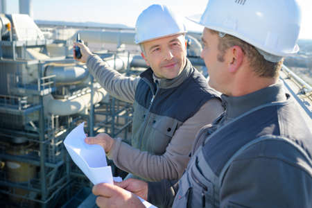 two male workers looking at plans overlooking industrial site Reklamní fotografie