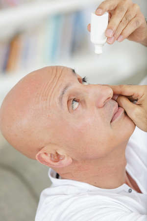 man applying eye drops to his eyes