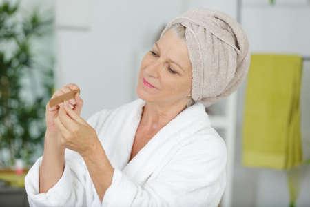 senior woman filing her thumb nail