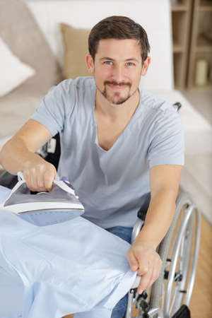 happy disabled man on wheelchair ironing clothing