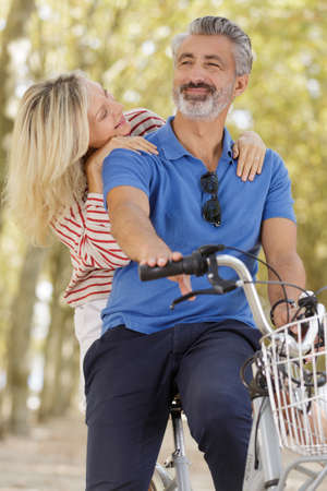 mature couple smiling on a bike