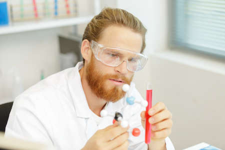 doctor or research scientist examines a test tube