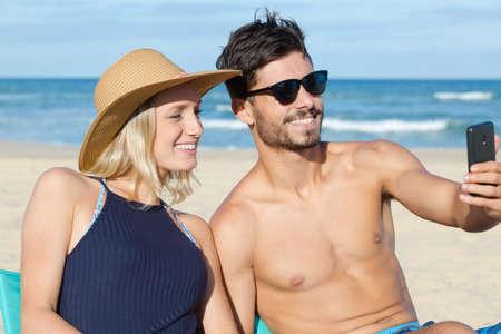 couple in love makes selfie beach