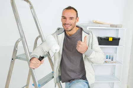 handsome young decorator with paint roller making thumbs up gesture Stock Photo