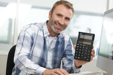 a smiling businessman holding calculator
