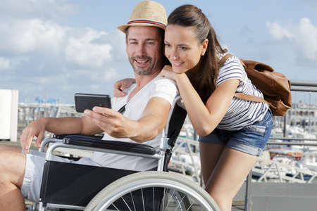 pleasant couple in the wheelchairs outdoors