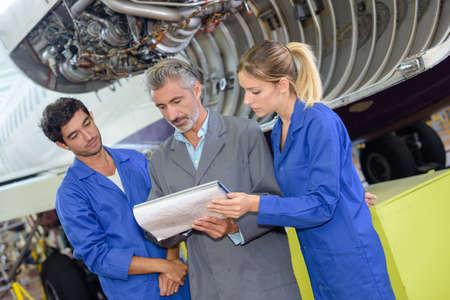 aerospace students with teacher in aircraft hangar