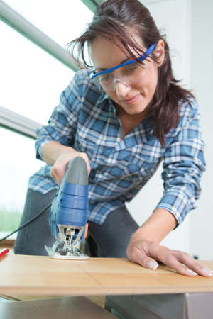 portrait of confident female carpenter using bandsaw in workshop