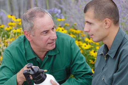mature gardener showing spray product to trainee