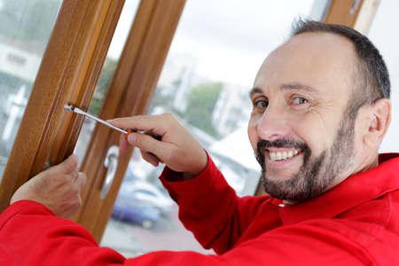 man screws a wood frame Banco de Imagens
