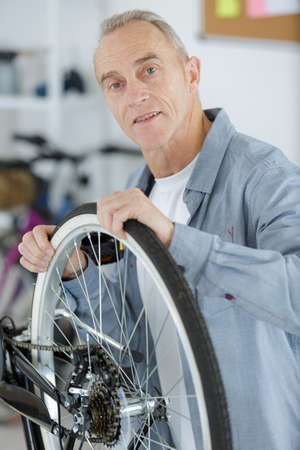 senior handyman fixing bike wheel in his garage