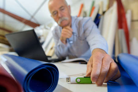 elderly man using a usb in office